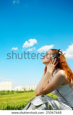 The girl in headphones listens to music in park - stock photo