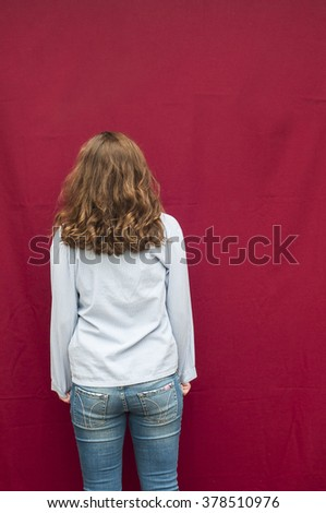 The girl in jeans and shirt stands with his back on the red background. Studio photo. Shorthair curly young girl. Fashionable jeans. Back view of teenage girl isolated on red background. - stock photo