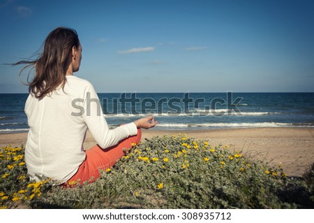 the girl in meditation on the beach in the Lotus position on a background of blue sky and blue sea - stock photo