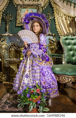 The girl in old-fashioned dress  with fan in beautiful room with gilded furniture - stock photo