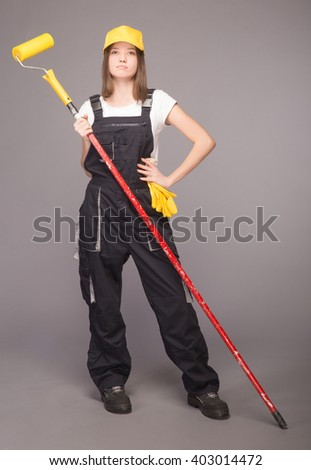 The girl in overalls in a baseball cap and gloves. One hand holds a long paintbrush. The second hand on the belt. Gray background.