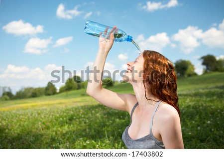 The girl in park pours over a face cold water - stock photo