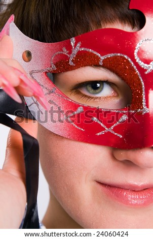 The girl in red carnival to a mask - stock photo