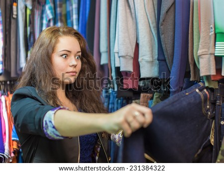 The girl in shop of clothes - stock photo