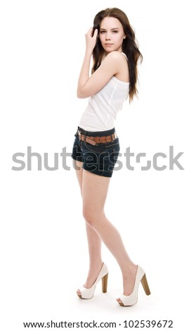 The girl in shorts standing on a white background