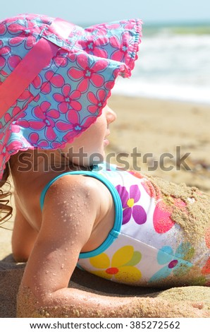 The girl in swimsuit  and hat  is  lying on the beach. - stock photo