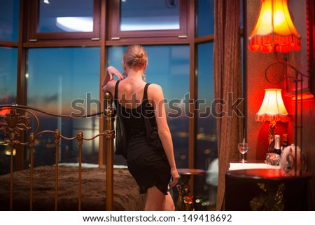 The girl in the bedroom look out the window at night cityscape - stock photo