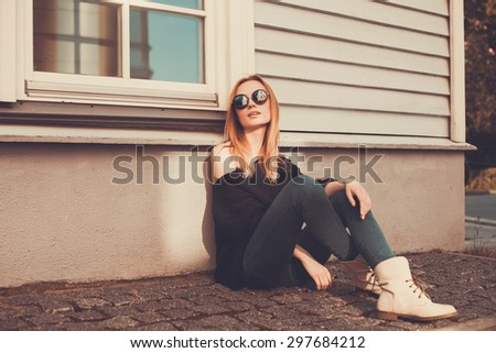the girl in the black sweater, sunglasses, jeans and boots sitting near the wall of the house on the street - stock photo