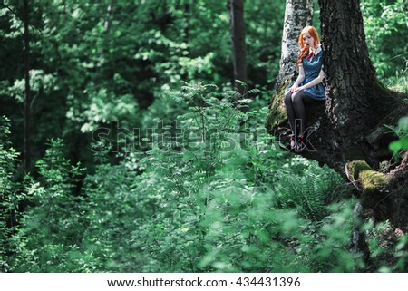The girl in the blue dress sitting on a tree. Birch roots. Woman on the background of a beautiful green forest. The lush green vegetation of summer. - stock photo