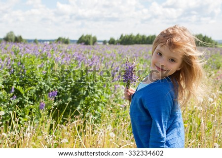 the girl in the field of flowers in the summer afternoon  - stock photo