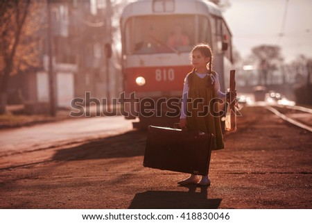 The girl in the green dress with the pigtails, with a loaf and a suitcase waiting for the tram one morning in the spring city at dawn. girl waiting for the train - stock photo