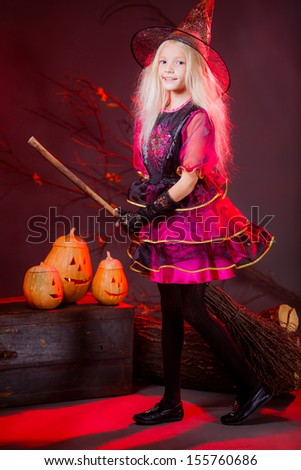 the girl in the image of a witch on a broom on Halloween in full growth