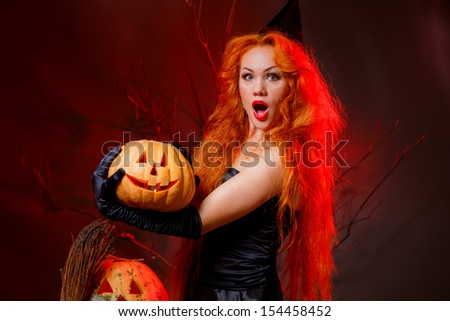 the girl in the image of a witch with a pumpkin on Halloween