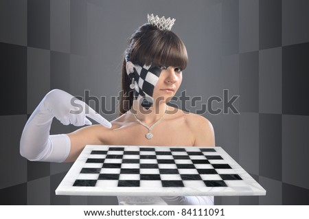 The girl in the image of the chess queen points to something on the chessboard, which she keeps - stock photo