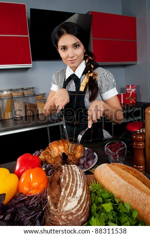 The girl in the kitchen by a uniformed chef cuts the Christmas turkey on the table with food