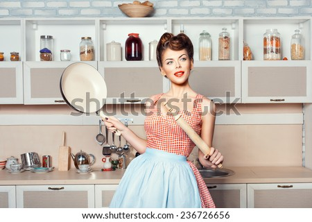 The girl in the kitchen in the hands holding pan and rolling pin. - stock photo