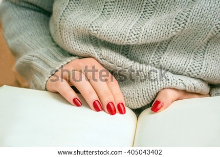 The girl in the knitted sweater sitting at the table reading a book. Closeup. - stock photo