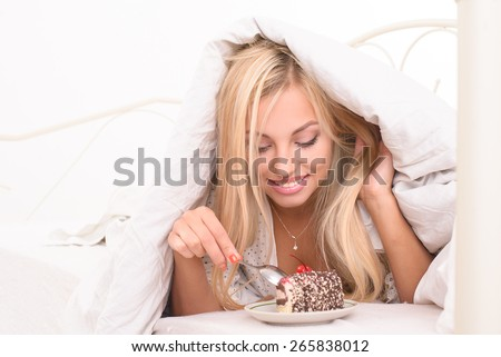 The girl in the morning, eat cake, not getting out of bed - stock photo