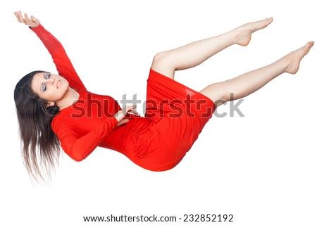 The girl in the red dress floating in the air his arms and legs, it is isolated on white background. - stock photo