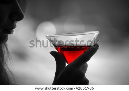 The girl is holding in his hand a glass of alcoholic beverage, red wine in glass ( black white photo) - stock photo