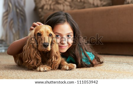 The girl is lying in the floor with the dog - stock photo