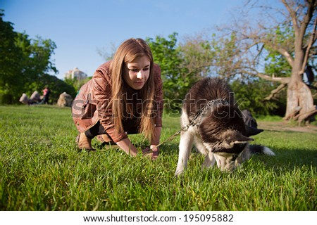 The girl is playing with her dog in the park while it is looking something in the grass