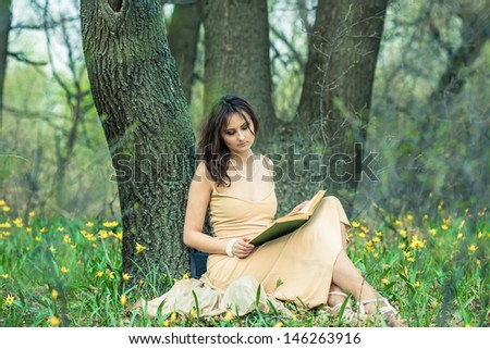 The girl is reading a book in the forest. She sits near a tree. There are a lot of flowers around.