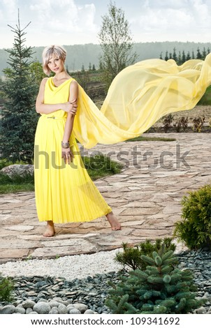 The girl is sitting on a stone in the park - stock photo