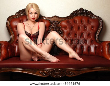 The girl is sitting on the couch. Leather sofa. Beautiful blonde. Frank clothing. - stock photo