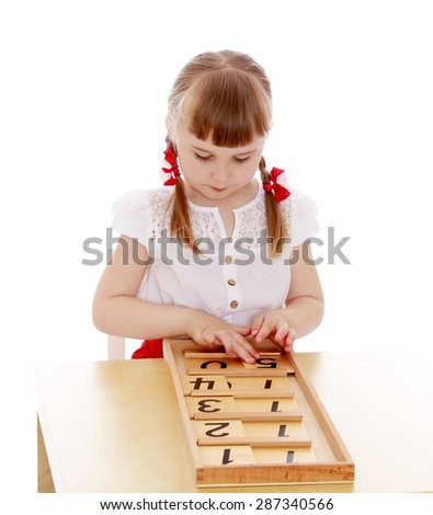 The girl is too young to attend school at the Montessori kindergarten is studying the figures sitting at the table-isolated on white background - stock photo