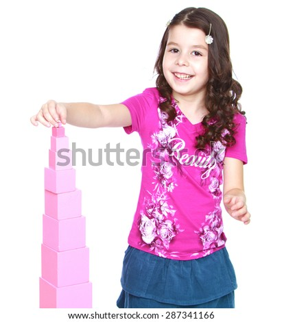 The girl is too young to attend school pink builds a pyramid in Montessori kindergarten-isolated on white background - stock photo