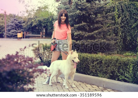 The girl is walking in the city with her husky dog. - stock photo