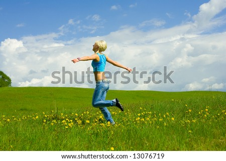 The girl jumping on a lawn