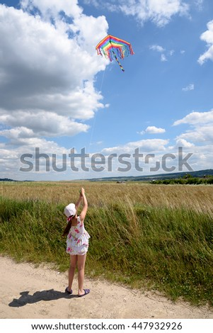 The girl launches a kite in field