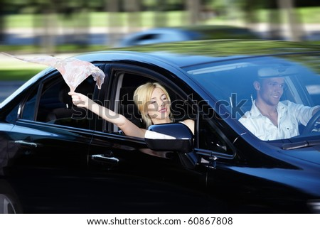 The girl let out of the car handkerchief swelling in the wind - stock photo