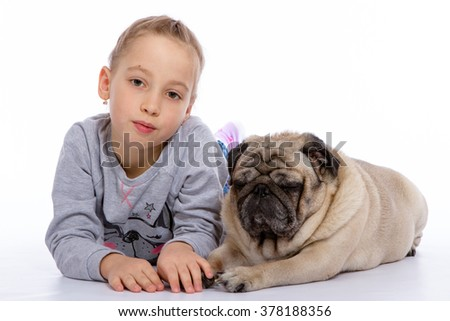 The girl lies near a dog on a white background