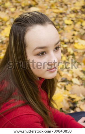 The girl looking in a distance in the autumn in park