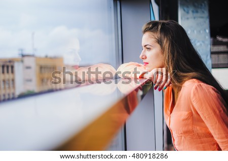 The girl looks at her reflection in the window . a young girl and f her long hair