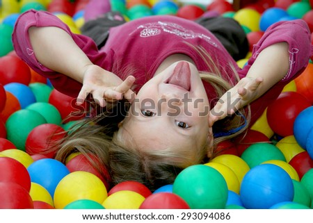 The girl makes a grimace Little girl playing with balls.  - stock photo