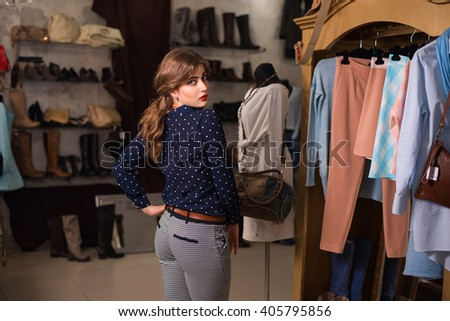 The girl measures clothes in shop