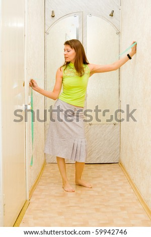 The girl measures width of a corridor in centimetre - stock photo