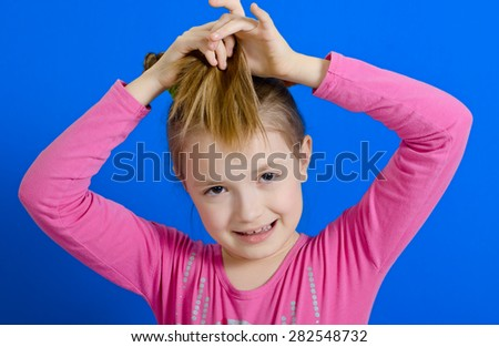 the girl of 9 years in studio plays with two braids. The photo on a blue background. - stock photo