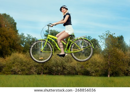 The girl on a bicycle in the park levitates over the meadow. She goes through the air without touching the ground. - stock photo
