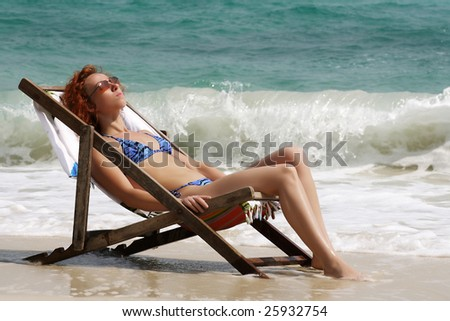 The girl on a chaise lounge on a background of the sea - stock photo