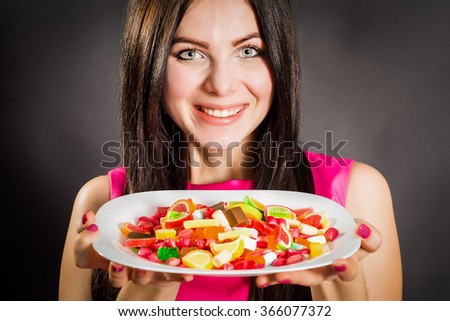 The girl on a dark background holding a plate of sweets and smiling