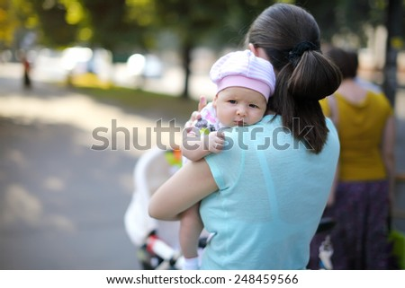 The girl on a shoulder at mother. Portrait - stock photo