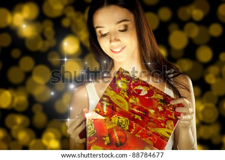 The girl opens the gift for the holiday. - stock photo