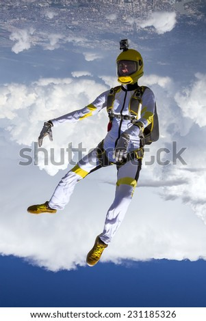 The girl parachutist performs figure freestyle in freefall. - stock photo
