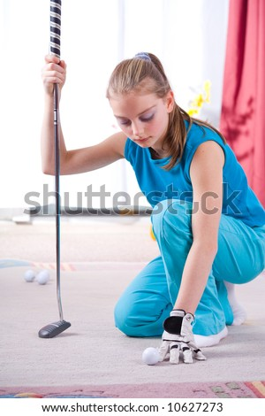 the girl playing golf in the living room - stock photo
