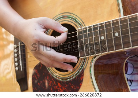 The girl playing guitar in her free time hand focus.